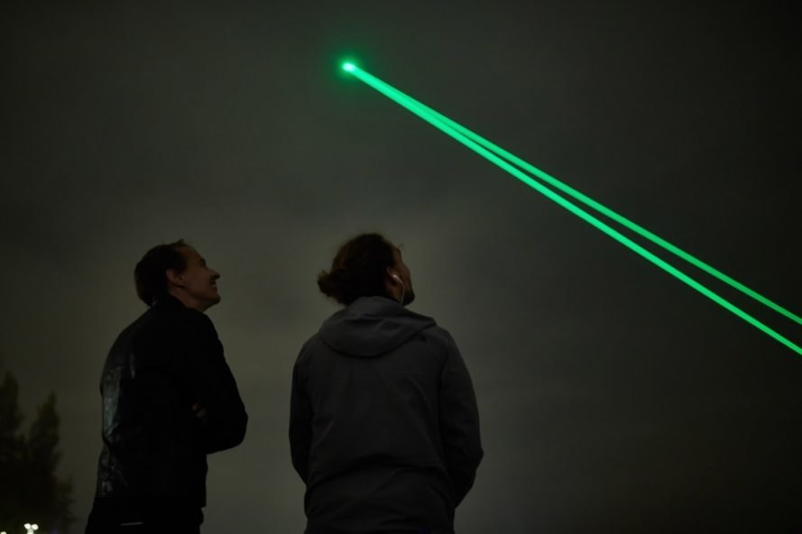 two people looking up at green laser light in dark sky
