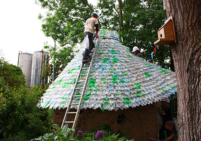 Volunteers recycle 7000 plastic bottles into a colorful for Building with recycled plastic