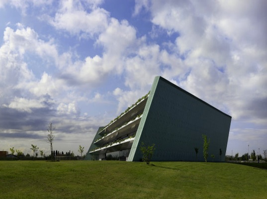 Trapezoid shaped eye bank building hugs a slope of stepped for Architecture originale
