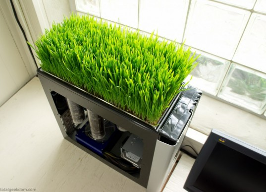 A desktop PC case with grass growing on top of it.