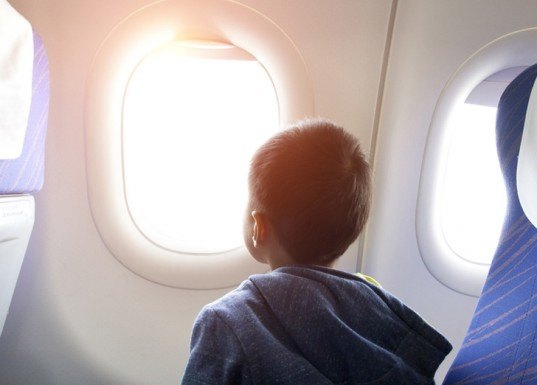 kid looking out airplane window, airplane window