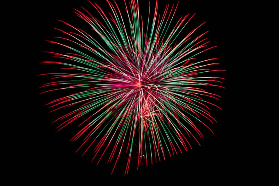 A red, white and green firework exploding