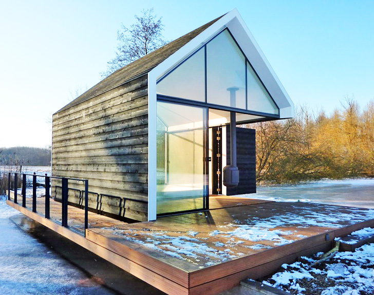 tiny glass and timber cabin cleverly folds open to blend