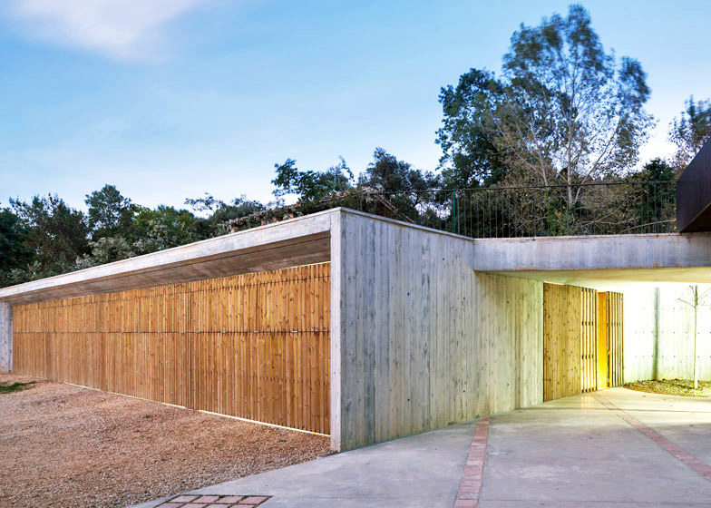 Green-roofed concrete outbuilding is an extension of the rural Spanish landscape