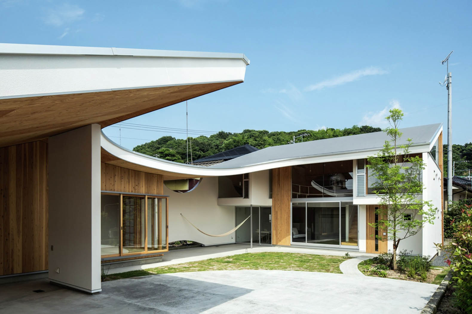 A gentle blanket-like roof covers the daylit interiors of this family house in Japan