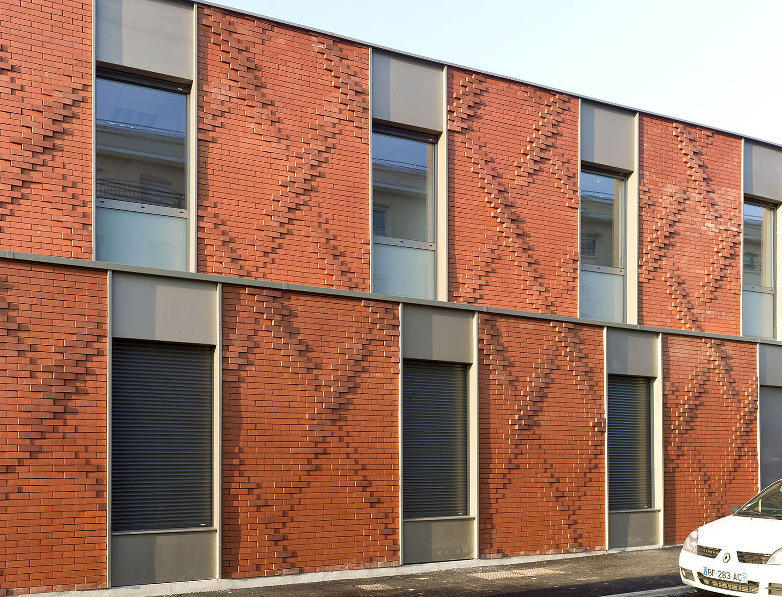 A surprising tapestry of brick clads the house for for Brick facade house