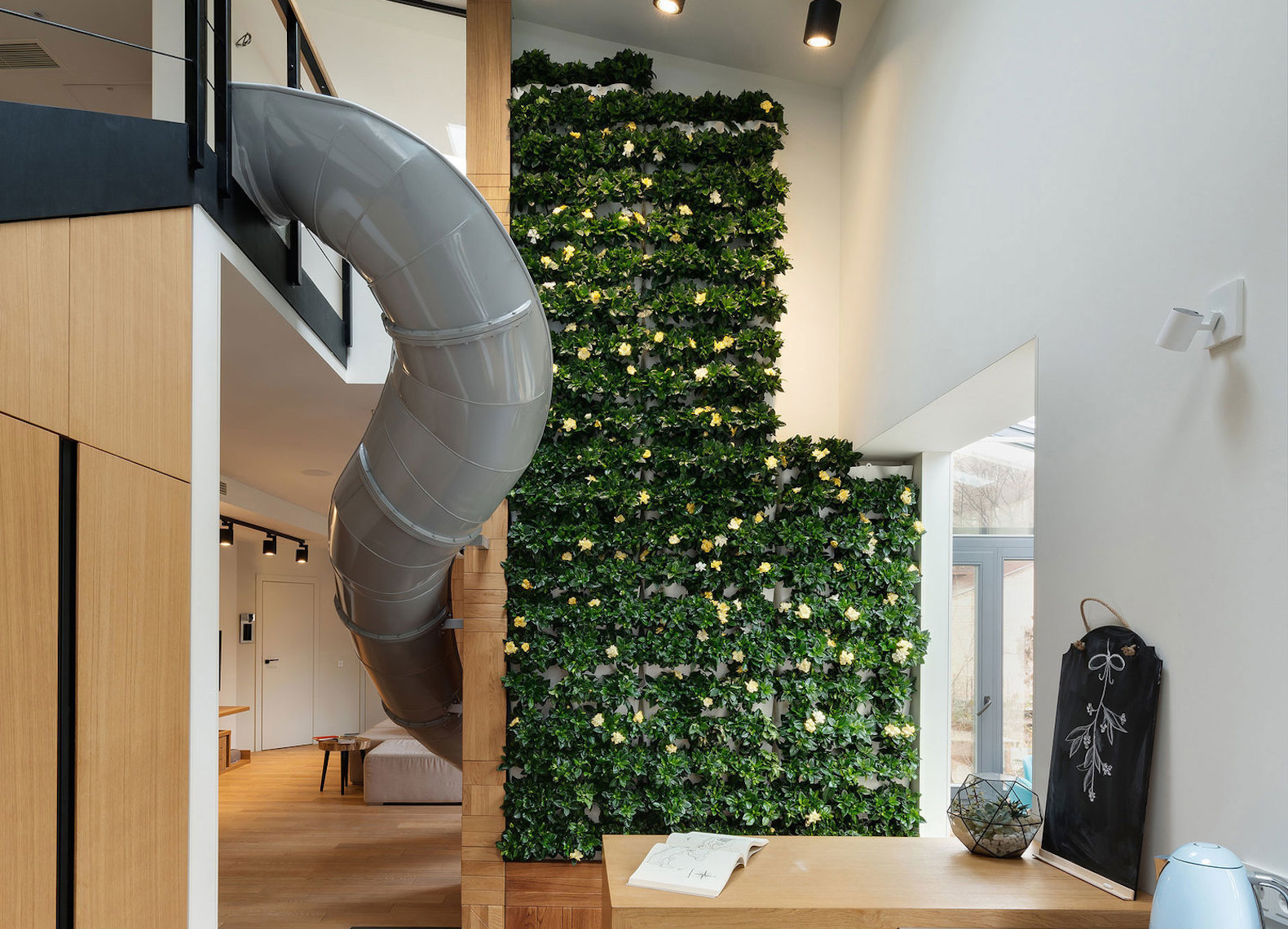 Funky slide cuts through this modern-chic apartment in Ukraine