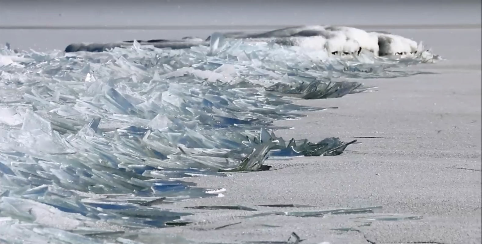 Watch frozen ice sheets from Lake Superior float ashore like shards of glass