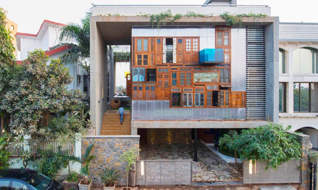 A colorful facade of recycled doors and windows adorns for Recycled windows and doors