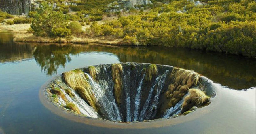 Conchos Dam in Portugal, Covão do Conchos, drain-like waterfall, portuguese waterfall, bell-mouth spillway, dam infrastructure, large lakes, portugal dams, dam design, lake infrastructure, nature, waterfalls portugal, vortex in a lake, vortex swallows lake water when it rains