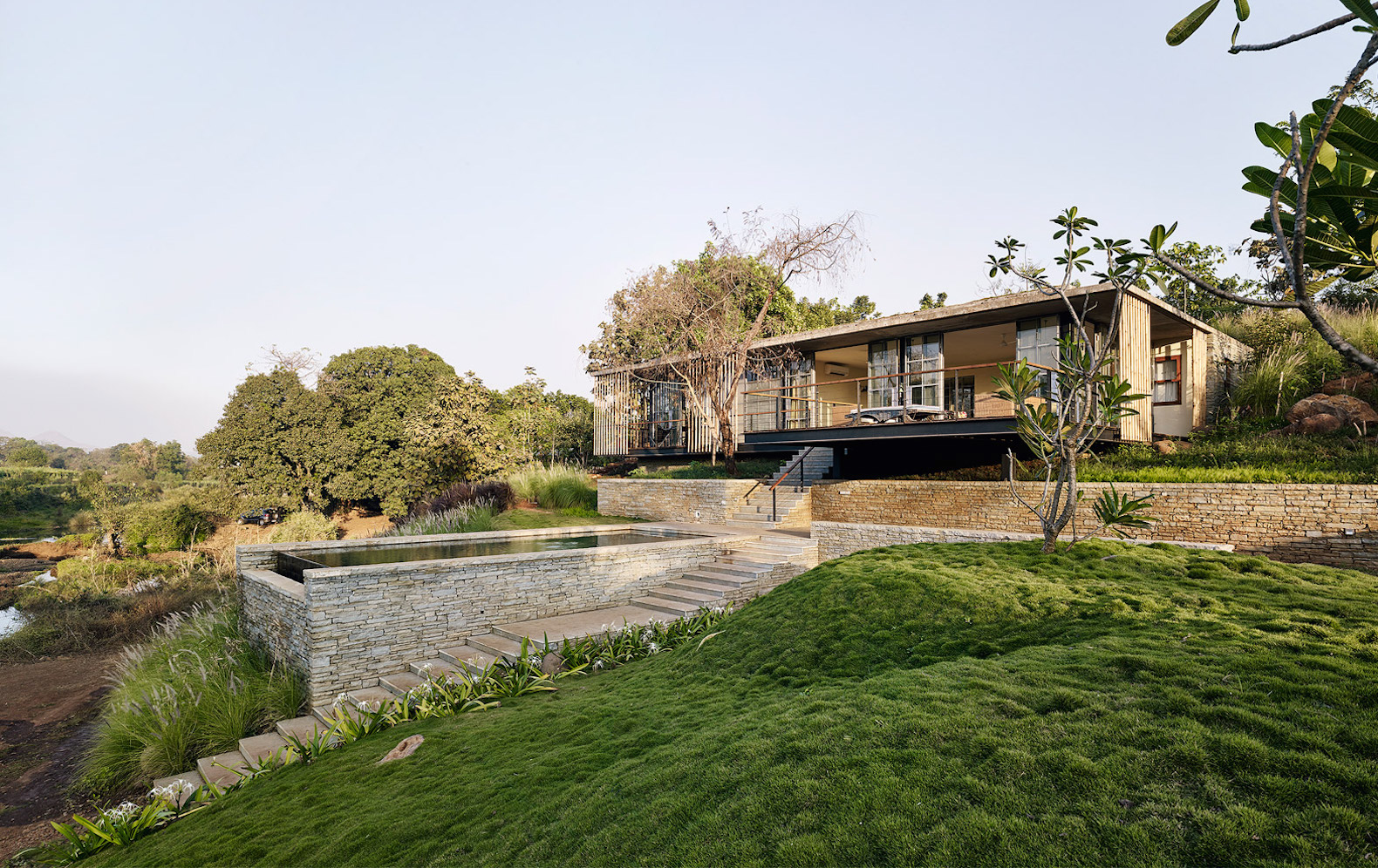Green-roofed home sinks into a beautiful UNESCO-protected riverside in India
