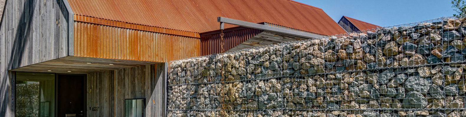 Gabion walls and recycled steel panels clad an outstanding for Salvaged building materials los angeles
