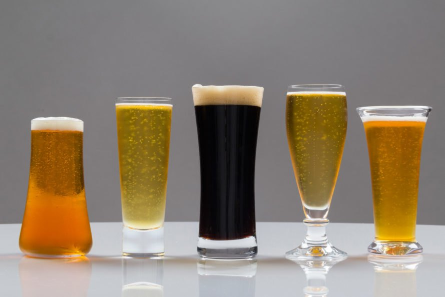 Five different shaped glasses with beer