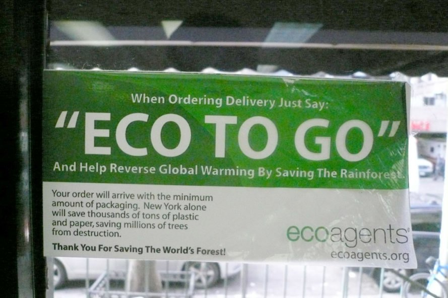"Green and white sign in a window that reads ""eco to go"""