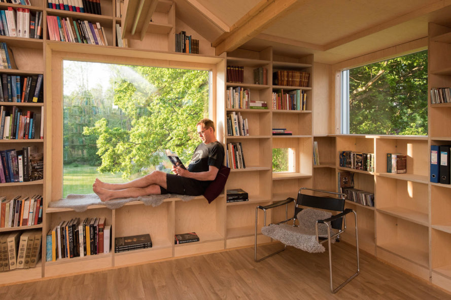 garage converted to library, garage conversions, Tjøme garage library conversion by NOMA Architects, tree-house like library, floor to ceiling bookshelves