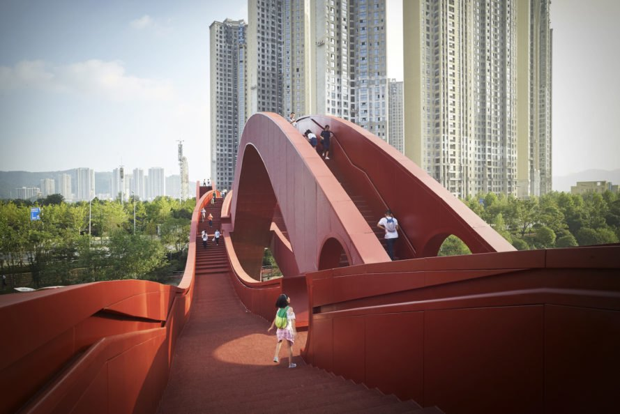 "Spectacular bridge in China is twisted like a Möbius Strip When NEXT architects first unveiled images for their extraordinary Lucky Knot bridge, the Möbius Strip-inspired designs seemed too good to be true. But just a few weeks ago, fantasy became reality with the opening of the Lucky Knot bridge in Changsha, China. Bridging local context and culture with modern design and technology, the pedestrian bridge is a unique work of art that challenges how we see and design everyday infrastructure. Located in the megacity Changsha's rapidly developing New Lake District, Lucky Knot spans the Dragon King Harbor River and serves as an auspicious icon for the region. The steel-framed bridge stretches 185 meters in length and 24 meters in height and is painted red—a color symbolizing good luck and happiness in Chinese culture. The bridge's unusual shape combines the principles behind the Möbius Strip and Chinese knotting, a decorative handicraft art typically made with red rope, and often used as auspicious wall hangings. The Lucky Knot's eye-catching design isn't the only way it stands out from most pedestrian bridges. Public engagement was a big focus of the design, which was crafted with recreational, ecological, and tourist activities in mind. Multiple landing platforms and cutouts, as well as the bridge's multiple swooping levels that connect to different heights like the riverbank and the elevated park, encourage a sense of play. An LED light show brings the bridge to life at night. The undulating bridge offers stunning views of the river, Meixi Lake, the city of Changsha, and the surrounding mountains. ""The Lucky Knot is more than a bridge and a connection between two river banks. Its success lays in bringing cultures together, and in the fusion of history, technology, art, innovation, architecture and spectacle,"" said NEXT architects Beijing partner Jiang Xiaofei. Changsha, Lucky Knot, NEXT architects, LED, pedestrian bridge, bridge, bridge design, infrastructure, China, Mobius strip, Mobius ring, auspicious design, Chinese knotting, Lucky Knot Bridge by NEXT architects, Lucky Knot bridge in Changsha, red bridge in Changsha, Mobius Strip-inspired architecture, Mobius Strip-inspired bridge, extraordinary bridge designs"