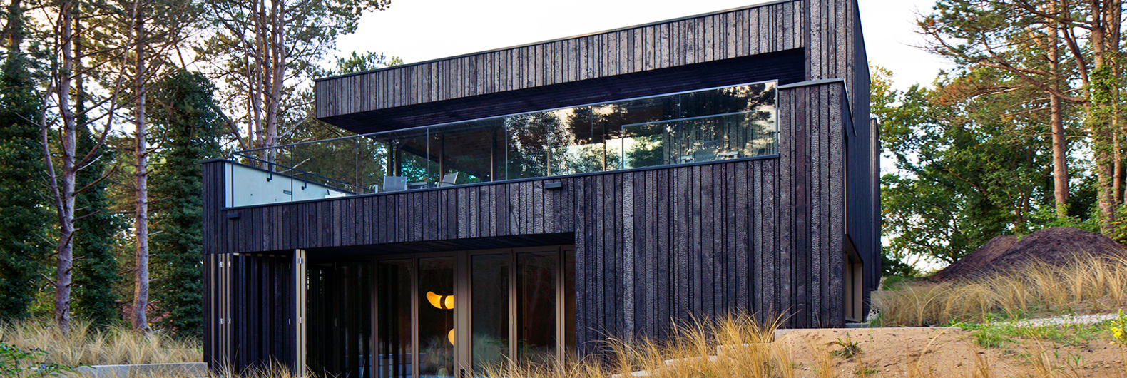 Zero-energy timber and steel home is buried into a natural dune
