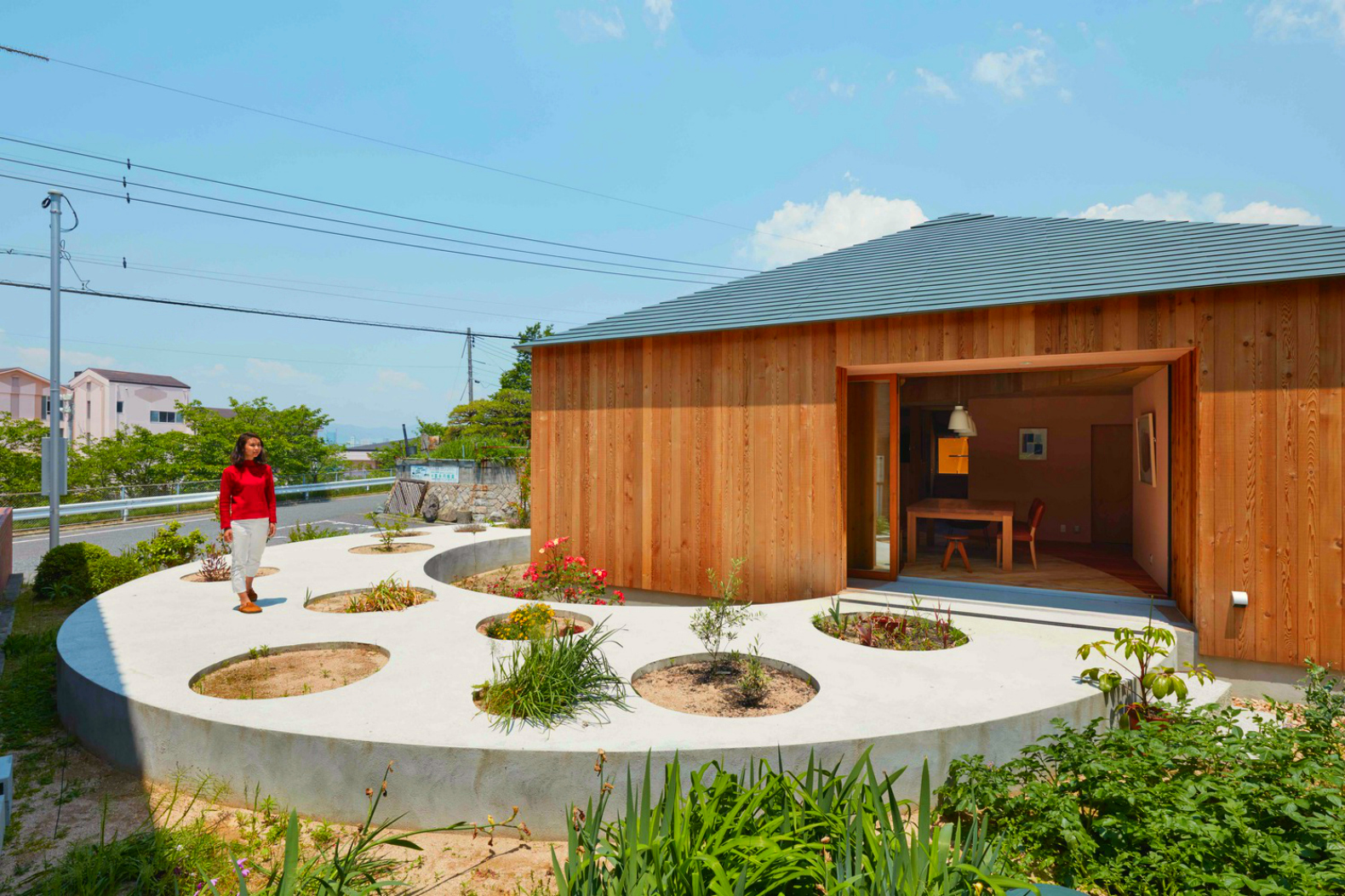 Circular garden walkway cuts straight through Japanese timber home