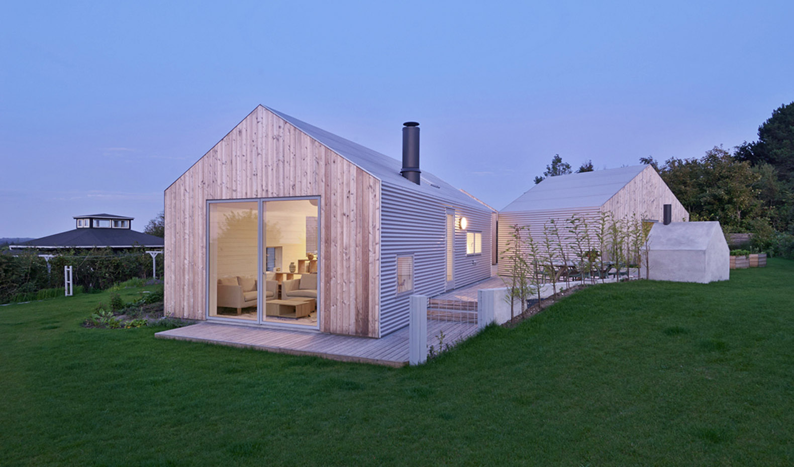 Five small buildings and a shared courtyard create a for Summer homes builder