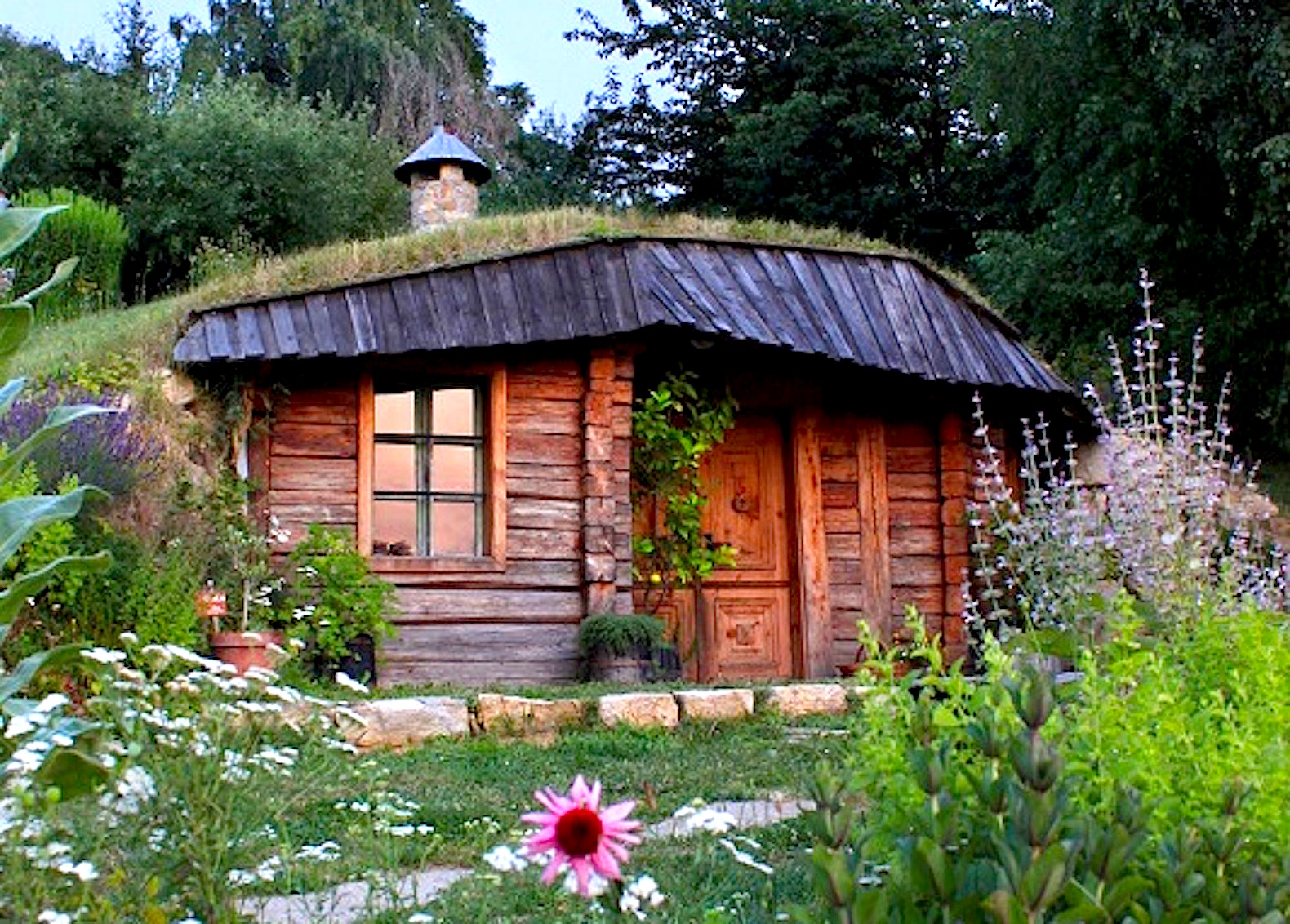 small wood home with grass roof surrounded by flowers