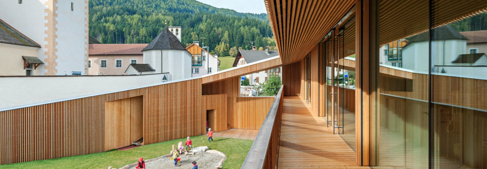 This timber kindergarten is embedded into the hills of a small ...