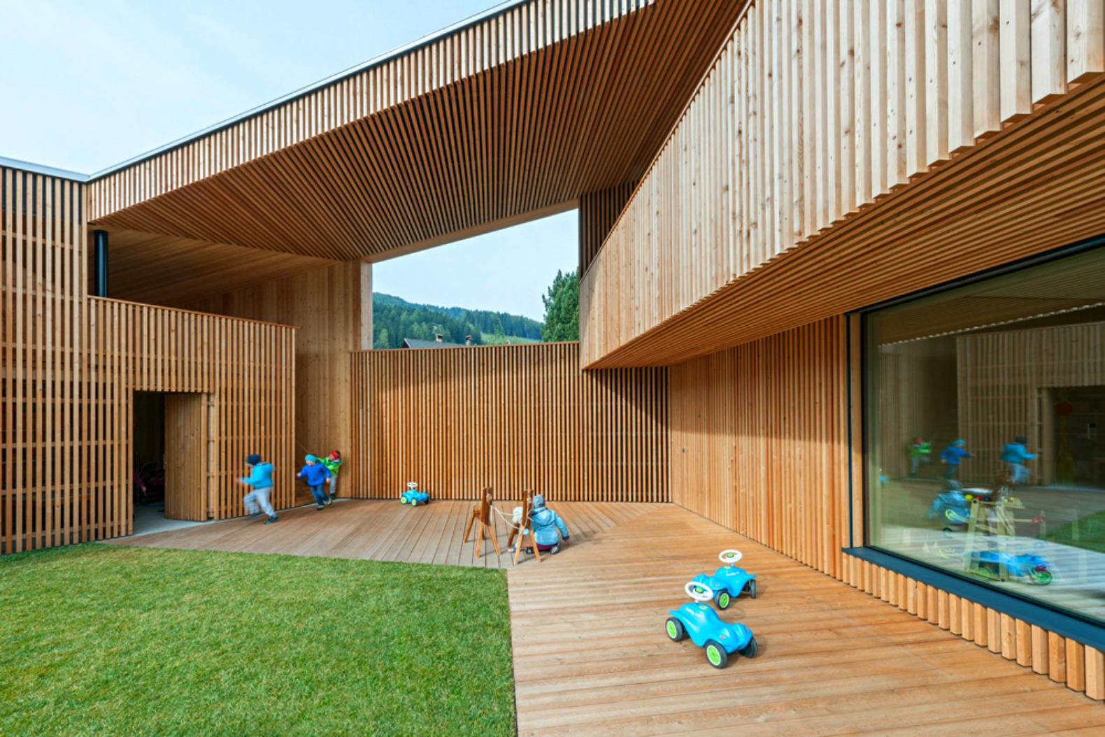This timber kindergarten is embedded into the hills of a ...