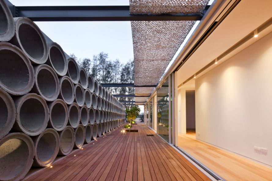 Screens Made Out Of Raw Concrete Pipes Provide Privacy For