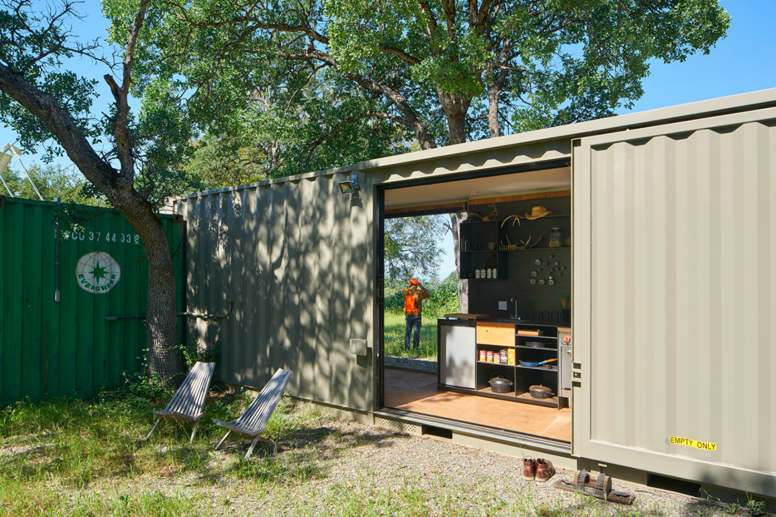 Off-grid shipping container cabin has a warm wooden interior