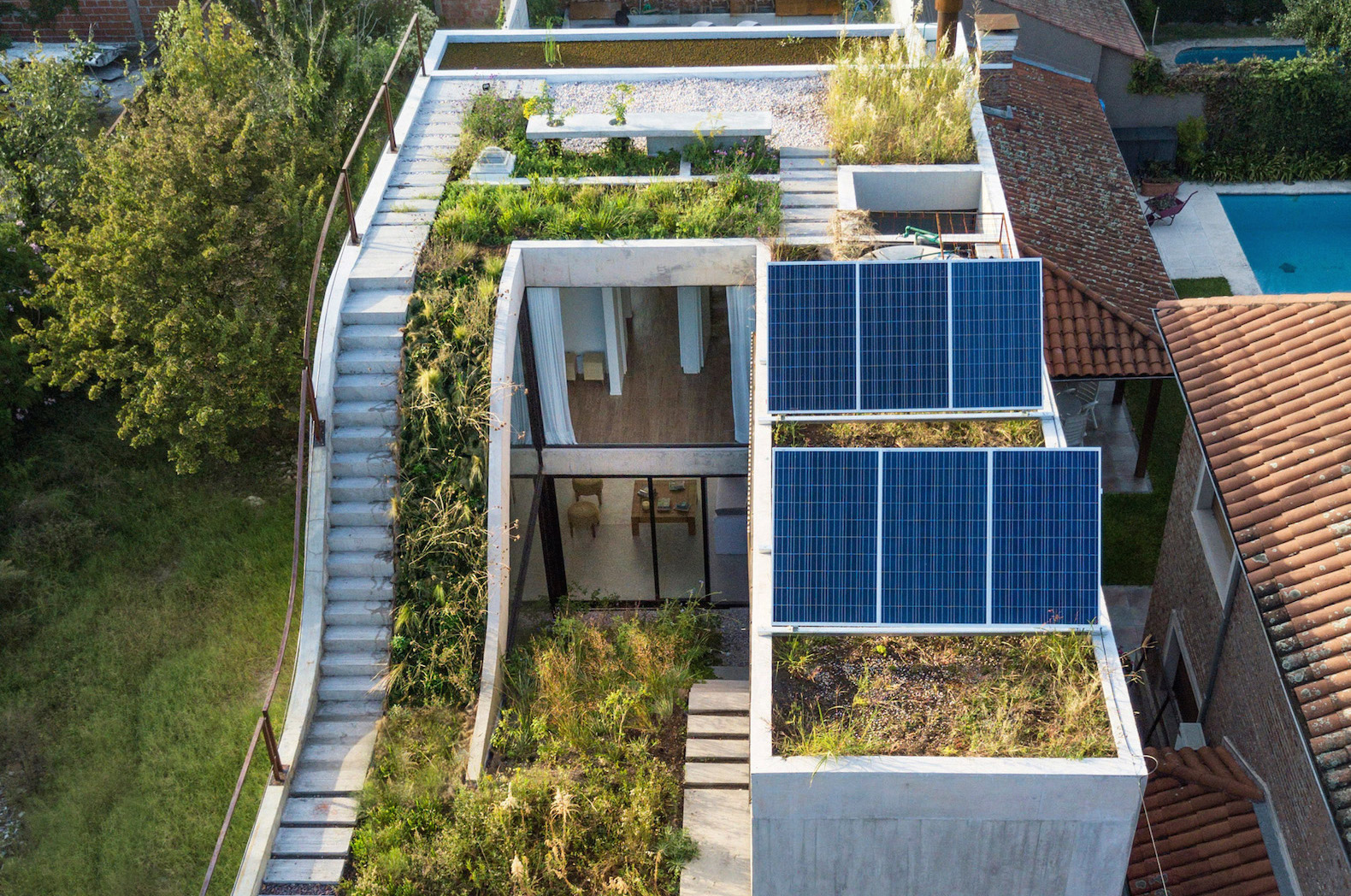 Luxurious solar home wraps around a sloped green roof