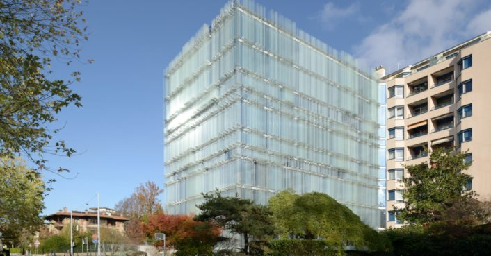 Naturally-ventilated glass building looks like a shimmering urban mirage