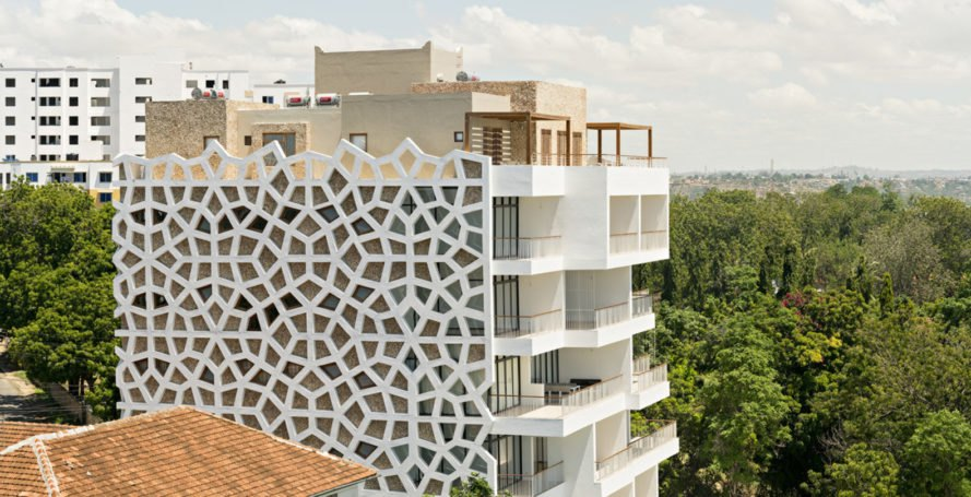 Tudor Facade a lacy skin fills this kenyan apartment building with sunlight and