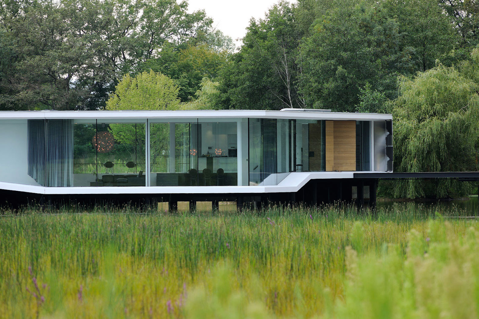 """Curvaceous geothermal-powered home """"floats"""" on a French lake"""