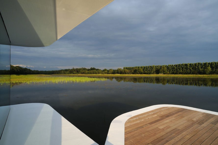 White Snake House by AUM, White Snake House, White Snake House in France, geothermal energy lake house, solar powered lake house, minimalist glass lake house, wraparound glazing lake house, concrete and glass lake house,