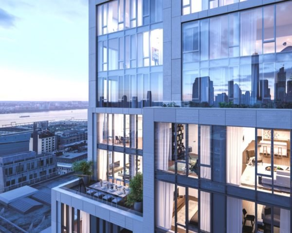 Image shows the exterior of 570 Broome at dusk. The building has tall floor-to-ceiling windows. and is surrounded by impressive views of New York City's buildings.