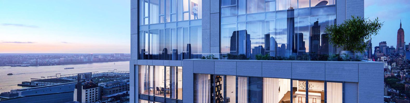 Image shows the exterior of 570 Broome at dusk. The building has tall floor-to-ceiling windows. and is surrounded by impressive views of New York City