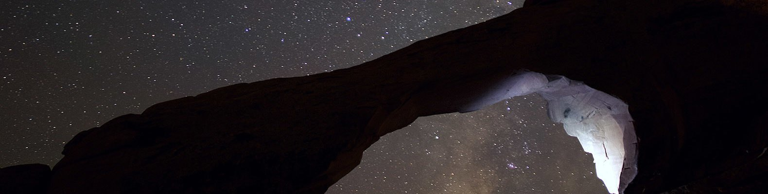 A natural arch formation against a starry sky