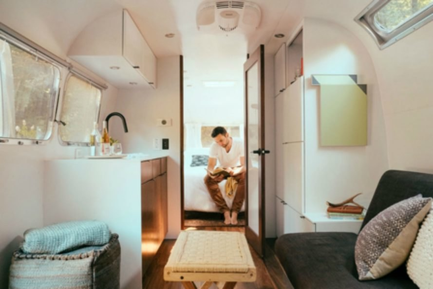 A man sitting on a bed inside an Airstream camper.