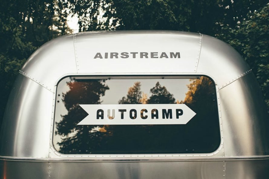 The rear windshield of a camper with the AutoCamp logo.