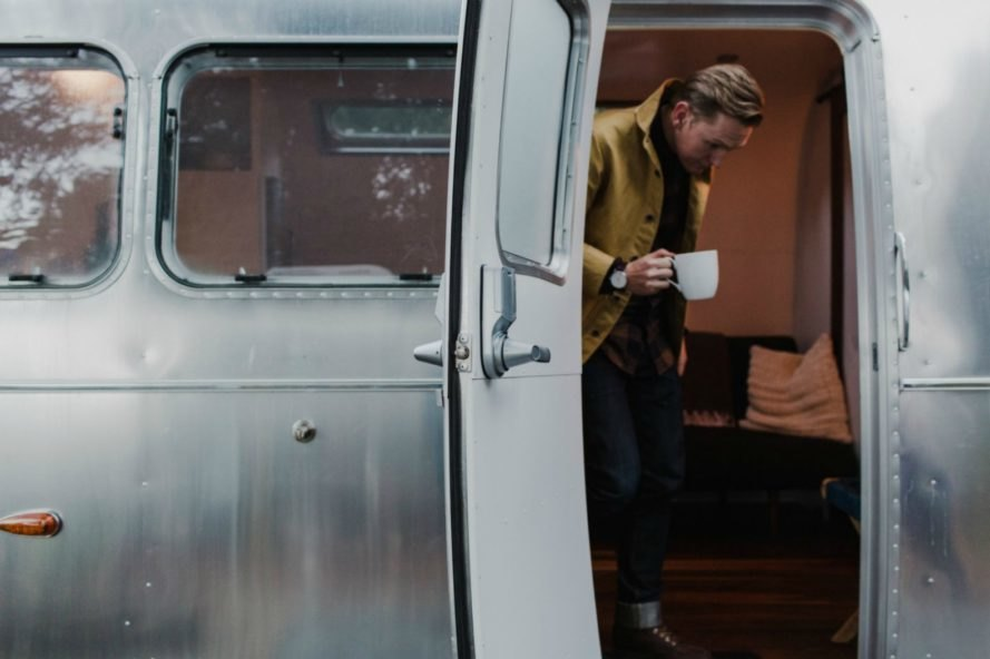 A man drinking coffee as he leaves an Airstream trailer.