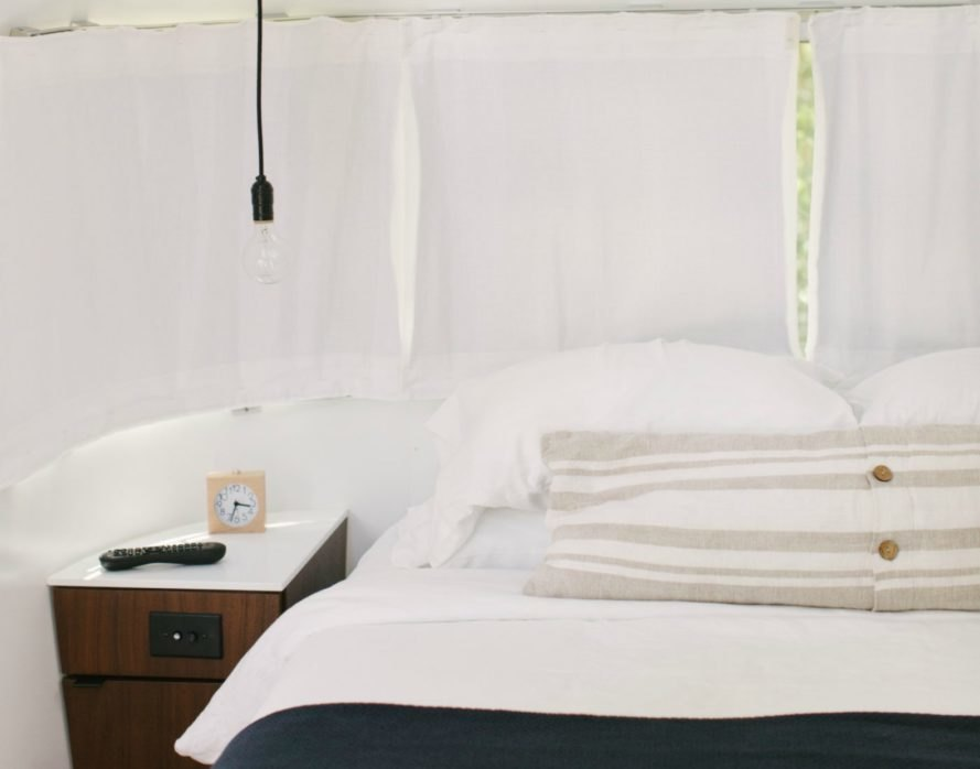 A queen-sized bed with white sheets and a nightstand.