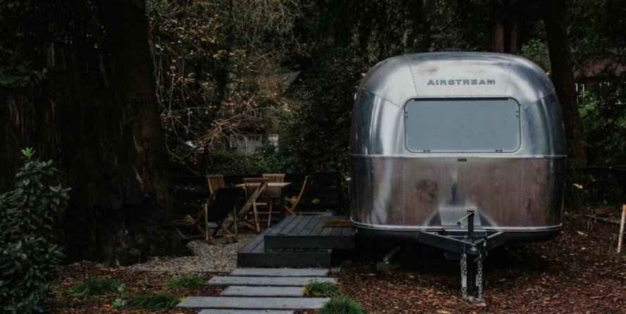 The back of a renovated Airstream camper with steps leading up to the entrance.
