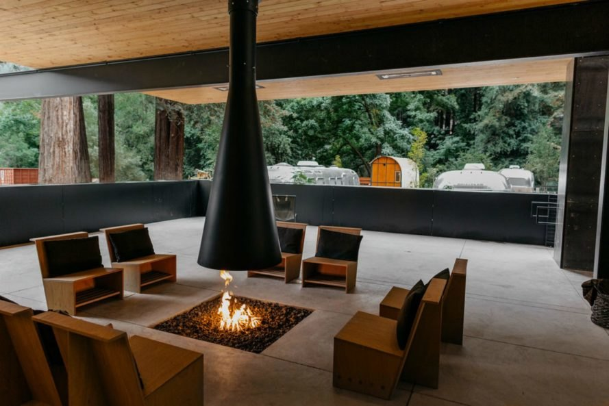 A lounge area with chairs around a campfire.