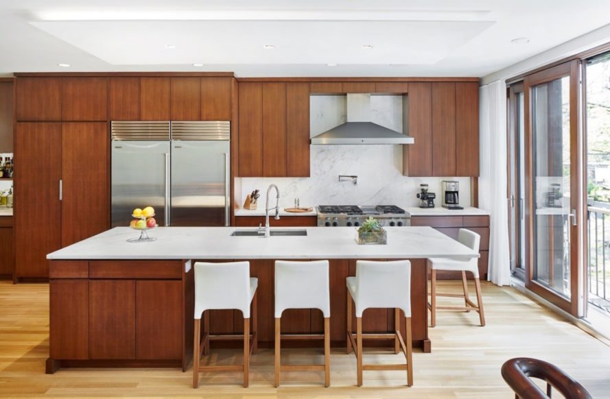 Modern kitchen, featuring wood cabinetry and a large island, in historic renovation Brooklyn passive plus house by Baxt Ingui Architects
