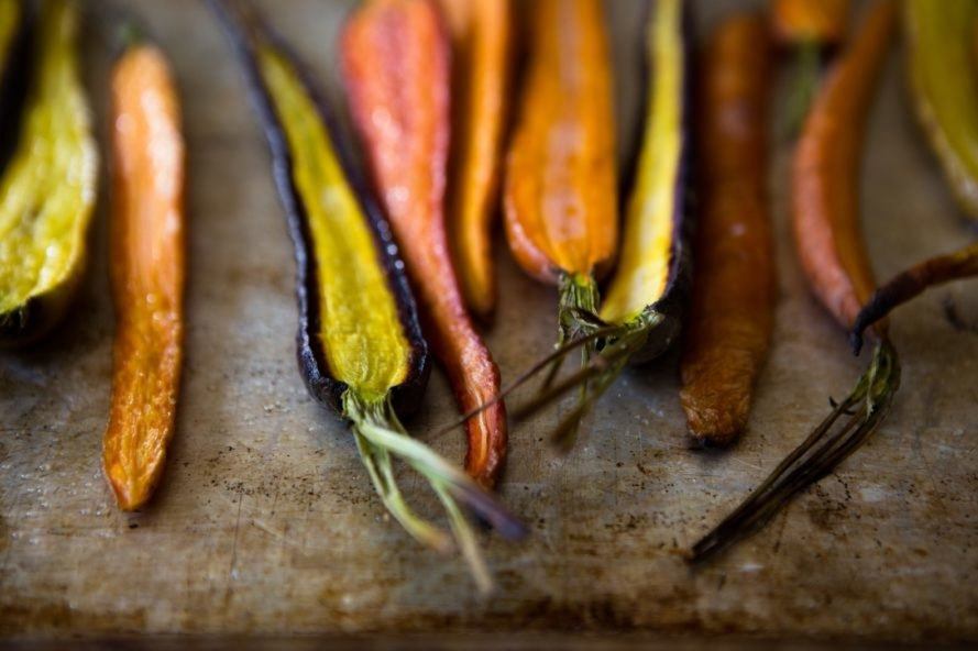 Multicolored roasted carrots rest on a baking tray