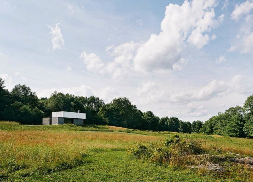 The concrete cabin sits on a vast amount of green land.