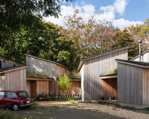 A cluster of wooden cabins in front of blossoming trees.