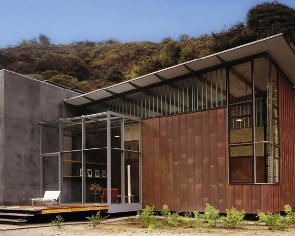 The home has large glass windows and is clad in copper and concrete