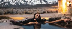 Man lounging in water with mountains in background