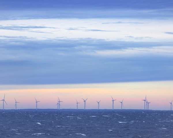 Offshore wind turbines in the sea at sunset