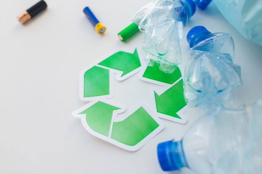 A green recycling logo with plastic water bottles and batteries